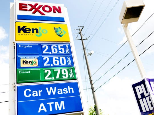 The sign displays gas prices outside of the Exxon Mobile