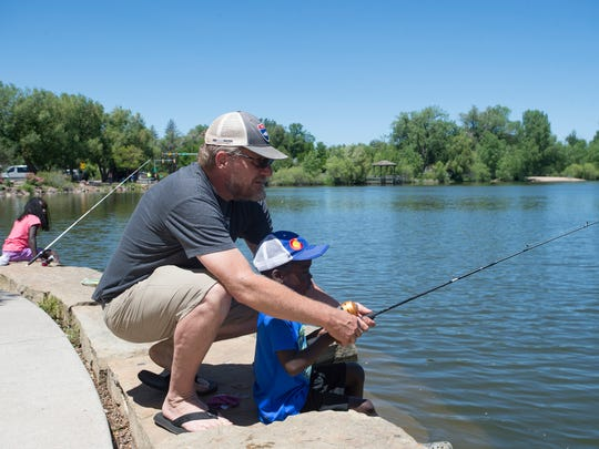 Jeff Borchert helps his son, Francis, 6, with his fishing pole as the pair fish with their family along the shores of Sheldon Lake in City Park on Friday.