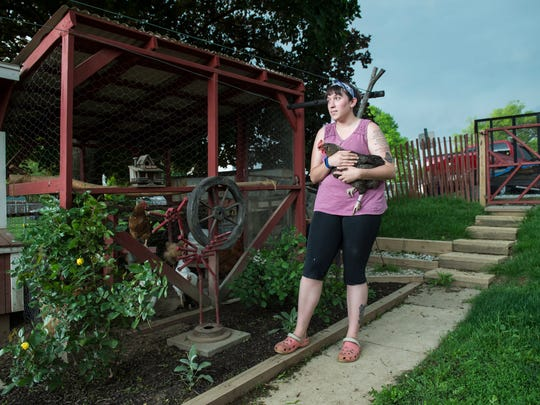 Ashlee Vandewater stands outside the chicken coop she built in the backyard of her Hanover Borough home. Vandewater, who owns 17 hens, is contesting a borough ruling that limits residential chickens to a maximum of four per lot.