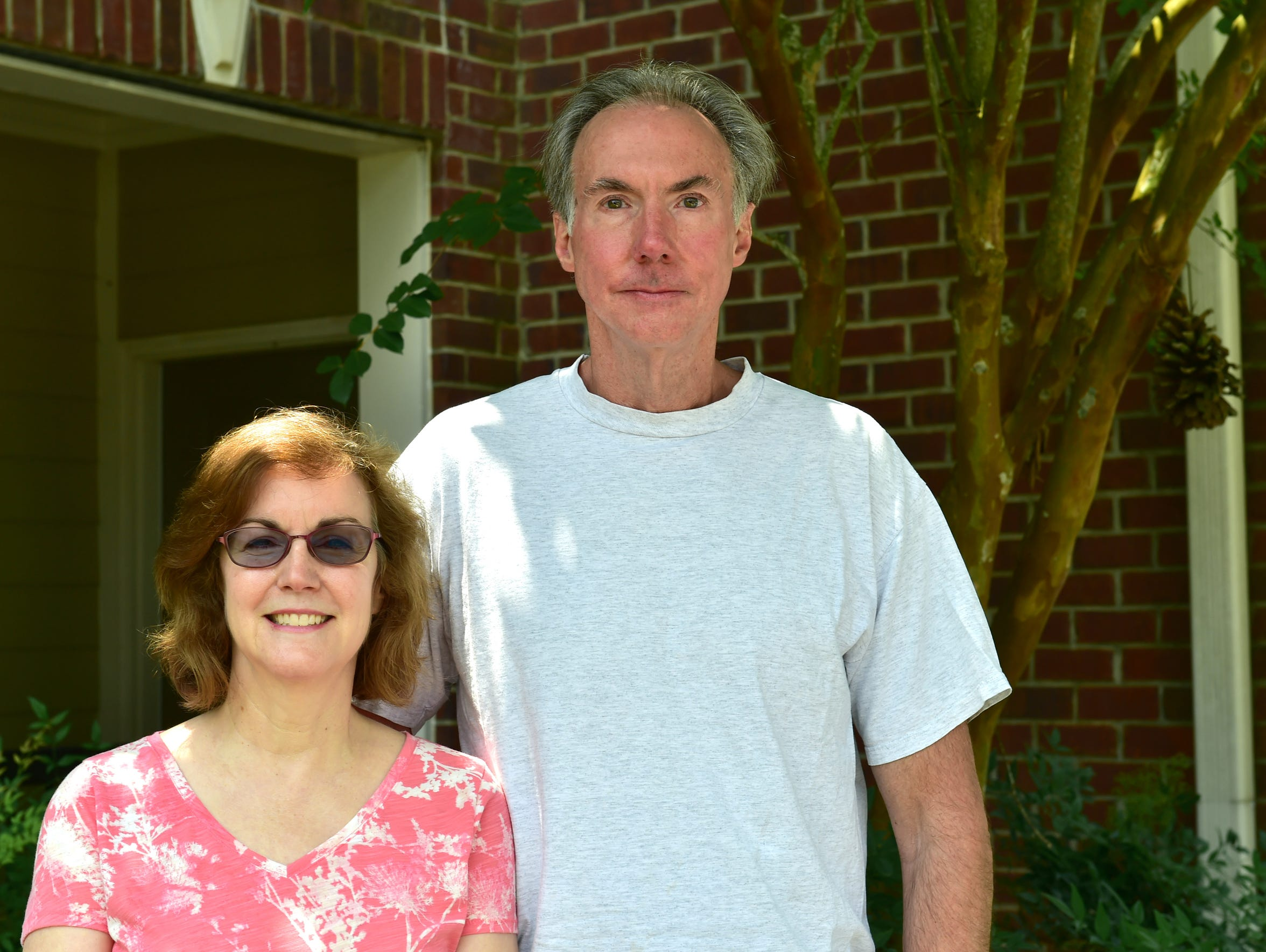 Jack Wayne and wife Catherine stand outside their apartment