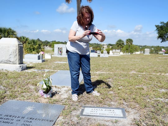 "Mari-Lynn Enns Herringshaw takes a photo of the new grave marker unveiled April 24, 2017, for Lucia Zora, a famed local circus animal trainer billed as ""the bravest woman in the world"" at Riverside Memorial Park in Fort Pierce. The grave remained unmarked since Zora's death in 1936 until Fort Pierce Mayor Linda Hudson, along with her sister Jean Wilson, discovered the gravesite while conducting genealogical research."