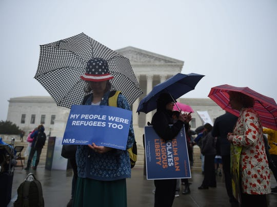 Protesters were outside the Supreme Court on a rainy day in April when the justices heard a challenge to President Trump's immigration travel ban.