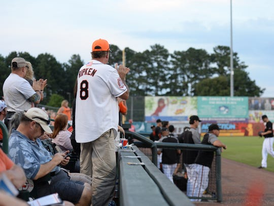 Fan Rod Reeves (center) stood to applaud as pitcher Chris Tillman left the Shorebirds game in the fourth inning.