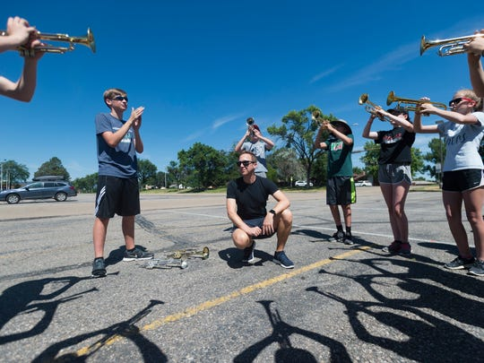 Nicholas Peterson listens as trumpet players of the Loveland High School marching band run through music during summer band practice in Loveland on Thursday, June 28, 2018. Peterson works as a counselor at Fossil Ridge High School in Fort Collins during the school year.