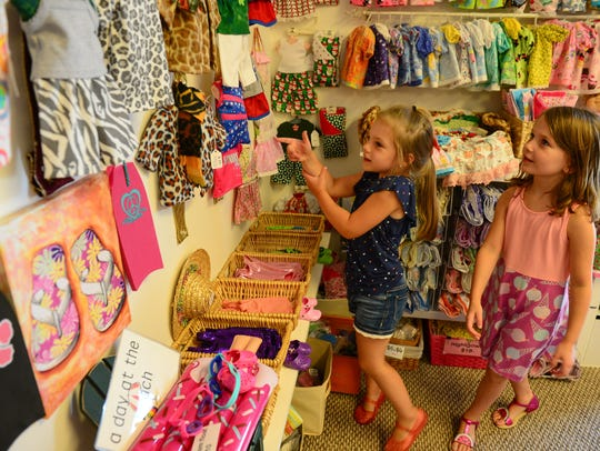 A two young girls checks out the clothing at The Doll