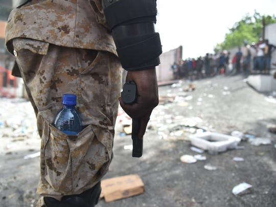 Haitian police arrive to control the looters in Delmas, a commune near Port-au-Prince, during protests against the rising price of fuel, on July 8, 2018.