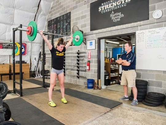 Leo Totten coaches Casey Rohrbaugh as she lifts during