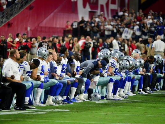 Dallas Cowboys take a knee before national anthem.