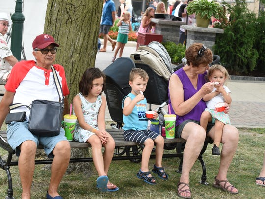 The Lomibao and Ross family enjoy the shade at Art in the Park in Plymouth.