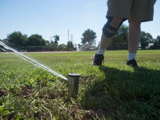 Ryan Shippy inspects a new sprinkler system at Bickling