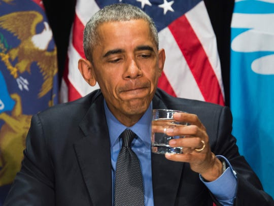 President Barack Obama drinks filtered water during a meeting at the Food Bank of Eastern Michigan in Flint, Mich., on May 4, 2016.
