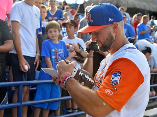 St. Lucie Mets designated hitter Tim Tebow (15) signs a football for a fan prior to the game against the Charlotte Stone Crabs at First Data Field.