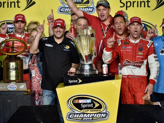 NASCAR Sprint Cup Series driver Kevin Harvick celebrates in victory lane with team owner Tony Stewart after winning the Ford EcoBoost 400 and clinching the Sprint Cup championship trophy at Homestead-Miami Speedway.