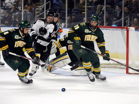 Vermont's Jonathan Turk, left, and Caylen Walls fight for a loose puck with Union's Matt Wilkins, center, during the first period of a game in the men's NCAA East Regional hockey tournament Friday, March 28, 2014, in Bridgeport, Conn.