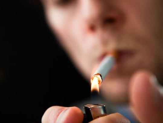 Man lights cigarette.