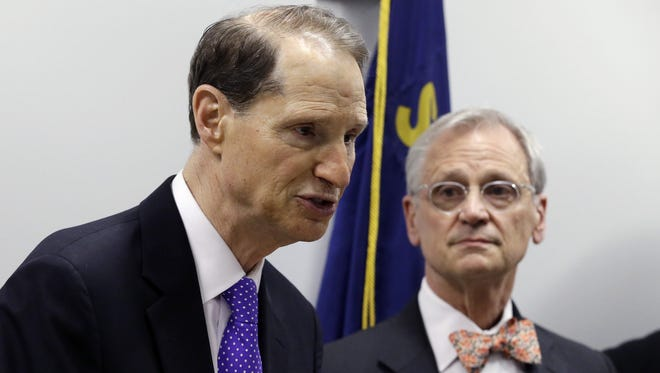 U.S. Sen. Ron Wyden, D-Ore., left, is backed by U.S. Rep. Earl Blumenauer, D-Ore., as he speaks at a news conference in Portland, Ore., Thursday, April 9, 2015.  The two announced plans to introduce federal legislation that would change Internal Revenue Code Section 280E, to allow state-legal marijuana businesses to take ordinary business deductions when computing their taxes. (AP Photo/Don Ryan)