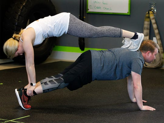 Courtney Tarmann and Nathan Kowalczyk demonstrate the partner plank exercises at bodyfuel inc. Eric Gramza designed this program to help couples prepare for their upcoming wedding.