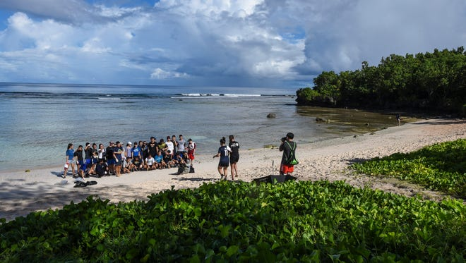 High school students take advantage of a group photo on a cleaner beach after their participation in the 23rd Annual Guam International Coastal Cleanup 2017 at Tanguisson Beach on Saturday, Sept. 16, 2017.