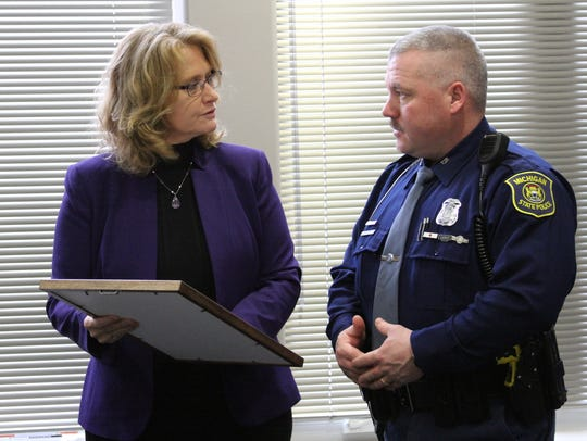 Michigan Rep. Lana Theis, left, presents an award Monday