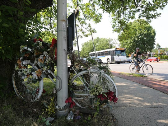 """A cyclist rides past a """"ghost bike"""" memorial for Merrill"""
