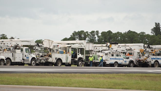 Dozens of utility trucks, many from out of state, stage at Witham Field Airport in Stuart to assist in the Florida Power & Light repairs Friday, Oct. 7, 2016, hours after the most powerful part of Hurricane Matthew passed the Treasure Coast offshore.