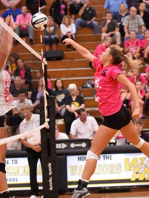 Granville's Christina Harrison tips the ball past a Watkins Memorial blocker during a match on Thursday, Sept. 28, 2017. The Blue Aces swept the Warriors. Both teams wore special jerseys for their Volley for the Cure night.