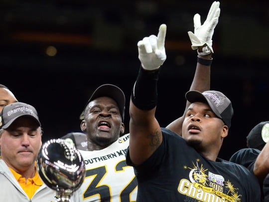Southern Miss defensive lineman Xavier Thigpen (32) celebrates with teammate Dylan Bradley, right, and coach Jay Hopson after the team's New Orleans Bowl victory last season.