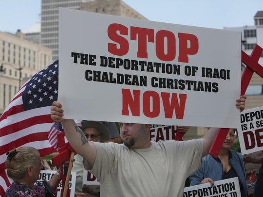 Jeremiah Suleiman, of Sterling Heights, holds a sign