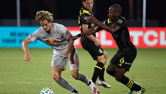 Midfielder Darlington Nagbe, right, said that as long as Crew players continue to test negative for COVID-19, he isn't thinking about opting out of the season.