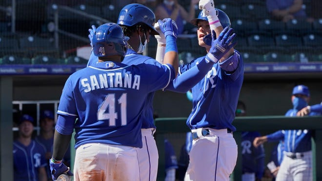 Kansas City Royals' Bobby Witt Jr., right, celebrates his home run with Seuly Matias, center, and Carlos Santana, left, in the fourth inning of a spring training baseball game Monday, March 8, 2021, in Surprise, Ariz. (AP Photo/Sue Ogrocki)