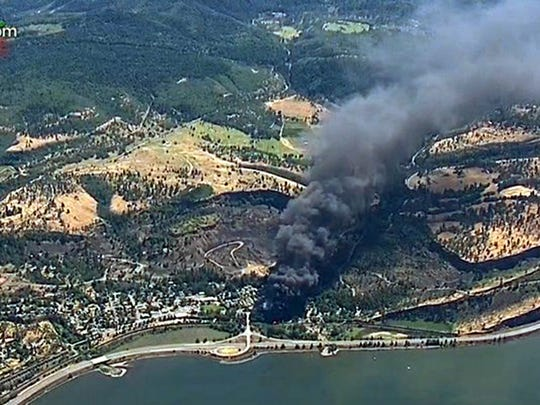 FILE - In this June 3, 2016, file image, from video provided by KGW-TV, smoke billows from a Union Pacific train that derailed near Mosier, Ore., in the scenic Columbia River Gorge. The derailment that released 42,000 gallons of oil and sparked a massive fire that burned for 14 hours is one of Oregon's top stories for 2016. (KGW-TV via AP, File)