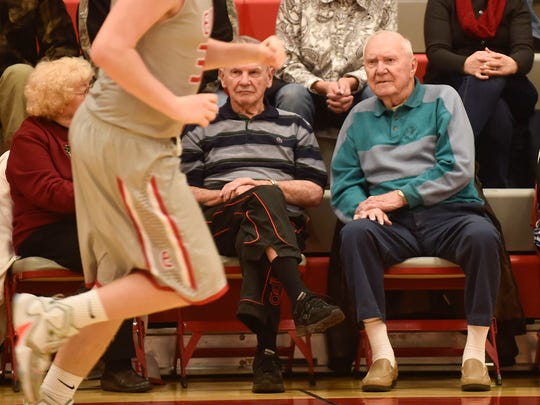 In the company of his brother to his right, Lowell Hensel, Green Camp High School's legend, who is now 87, watches as the Elgin boy's team plays East Knox on Thursday night. Hensel was honored before the varsity boys game.
