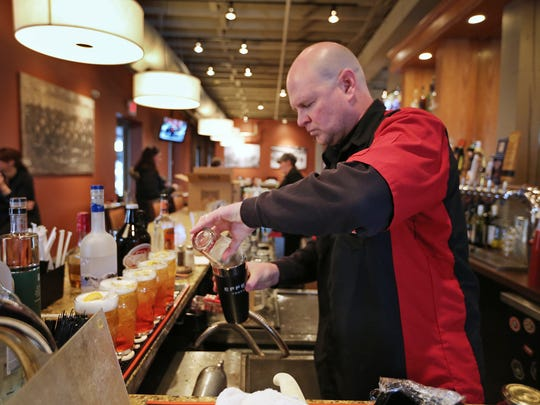 """Mike DeWeese, from Tow Yard Brewing, prepares his whiskey cocktail, """"American Hook Up,"""" during the Devour Downtown cocktail competition at Tavern on South, Tuesday, January 6, 2015."""