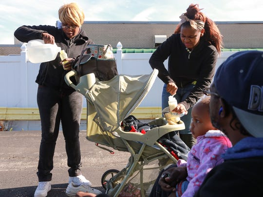 In this October photo, Dewayne Forney of Flint looks on while holding his daughter Vanessa Forney as 14-year-old Anjhe' Walker, center, and Estella Walker mix baby formula using bottled water in the parking lot of a restaurant in downtown Flint.
