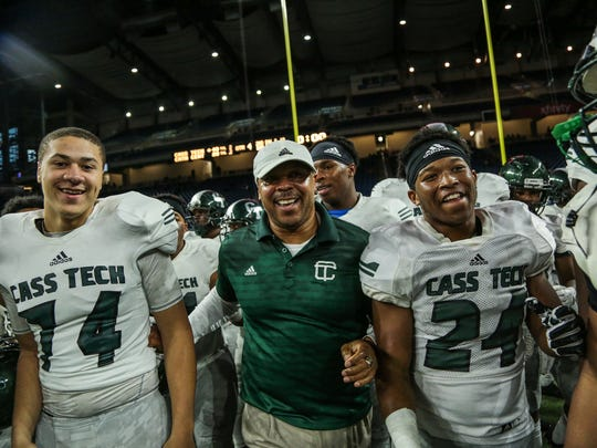 Detroit Cass Tech's players celebrate with head coach Thomas Wilcher winning the title against Detroit Catholic Central during the Division 1 High School Championship game on Saturday November 26, 2016, at Ford Field in Detroit, MI. Cass Tech won 48-20.