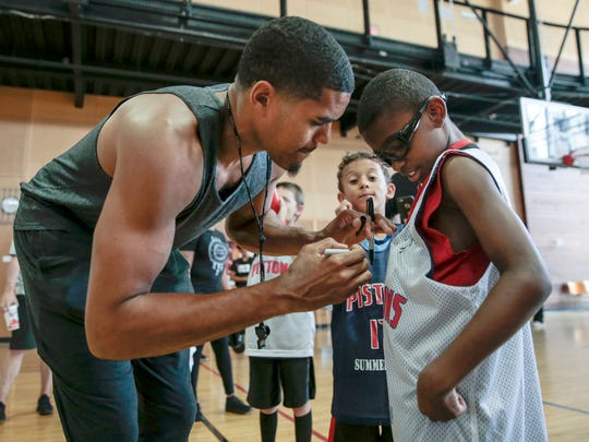 Detroit Pistons' Tobias Harris signs autographs for Jeremiah Grady, 10, of Warren during the Pistons Academy at the Boll Family YMCA, Thursday, July 6, 2017 in Detroit.