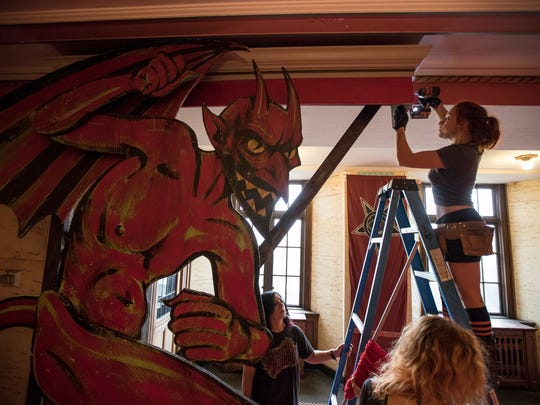 Theatre Bizarre building crew member Bridget Blondell, right, installs drapery at the entrance of Dirty Devil's Peepshow at the Masonic Temple in downtown Detroit, Friday, October 6, 2017.