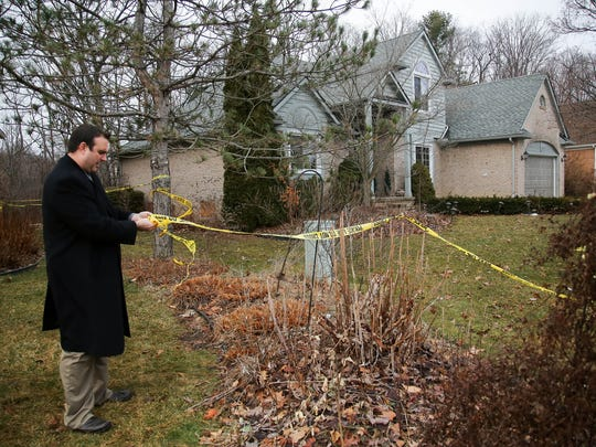 A Novi police detective secures the police tape around this home in the 23000 block of Mystic Forest Drive where five Mexican immigrants died in a house fire in February 2016.