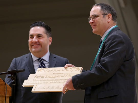 Joe O'Leary, left, the acting director of the Oregon Youth Authority, presents a plaque made by youth in custody to Randy Butler, a pastor with Salem Evangelical Church, during a dedication of a new gym floor at MacLaren Youth Correctional Facility in Woodburn on Thursday, Feb. 8, 2018. Salem Evangelical Church donated $110,000 to replace the old concrete gym floor at the facility with a new wood floor.