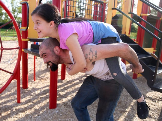 Luke Slaughter, 25, of Salem, plays with his stepdaughter,