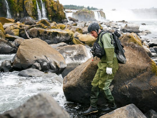 Matt Zimbrick looks for a route over the boulders and rushing water of Willamette Falls on Monday, July 9, 2018, in Oregon City. Zimbrick and a team of three were at the falls to harvest lamprey, a nearly 450 million year old fish that is culturally significant to tribes from southern California to Alaska.
