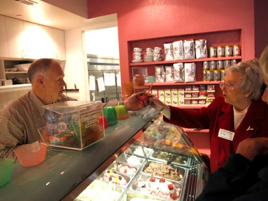 Coolato Gelato owner Allen Meuret, left, hands Gin