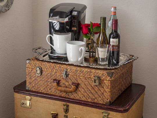 A stack of old suitcases holds a drinks service, with