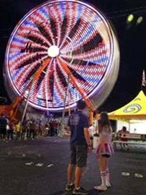 The Ferris wheel creates brilliant colors as it spins on the midway at the 2016 Tennessee State Fair on Sept. 17, 2016 in Nashville.