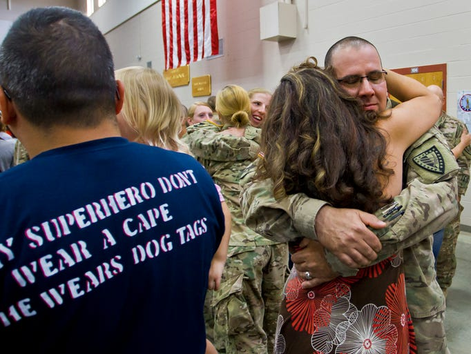Aaron Smeigh receives a hug from his wife Stephanie as he and other members of the 1638th Transportation Company return from Afghanistan Wednesday, July 16, 2014, at the National Guard Armory on  Haggerty Lane in Lafayette. The company returned after nearly a yearlong deployment in support of Operation Enduring Freedom. The Smeighs are from Richmond, Indiana.