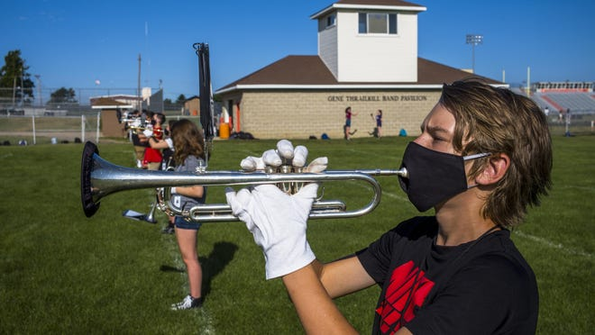 Troy Reiser joins other members of the Washington Community High School marching band for practice on Thursday in Washington. To comply with COVID-19 pandemic guidelines, band members wear specially designed masks that allow placement of the instrument against their lips and also use a cover over the bell of the instrument.
