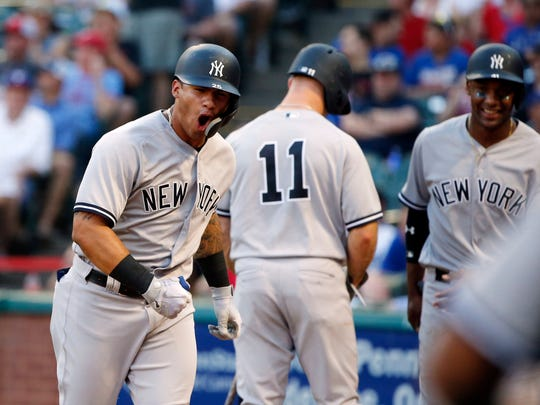New York Yankees Gleyber Torres (25) celebrates his three-run home run against the Texas Rangers with teammates during the fifth inning of a baseball game Wednesday, May 23, 2018, in Arlington, Texas.