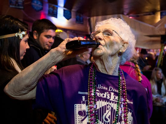 Sue Vasseur takes a shot of liquor as she greets guests at Fred's Lounge in Mamou, La., on Mardi Gras day.