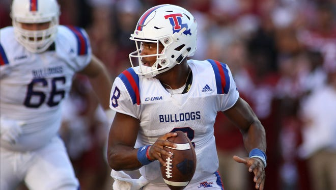 Louisiana Tech's J'Mar Smith looks for an open receiver after breaking a tackle during the fourth quarter of an NCAA college football game against Arkansas, Saturday, Sept. 3, 2016, in Fayetteville, Ark. Arkansas defeated Louisiana Tech, 21-20.
