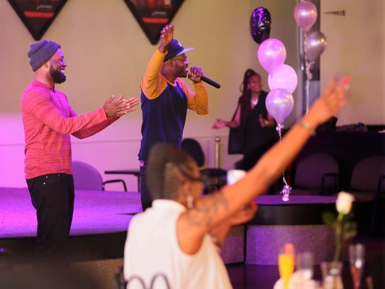 Dameion Perkins (left) and Nate Hamilton (center), the brothers of Dontre Hamilton, who was killed after an altercation with a Milwaukee police officer, perform a song at the brunch about how they felt after their brother's death.